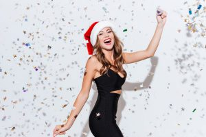 Model Celebrating in Santa Hat and Tight Black Dress