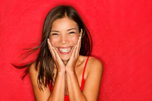 Female Smiling in Red Shirt on Red Background