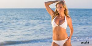 Blond woman at the beach wearing a white bikini
