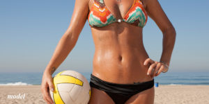Woman in a black and orange striped bikini at the beach holding a ball