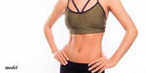 Female wearing a green sports bra showing her abdomen